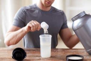 man making protein drink with powder