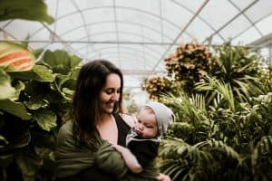happy mother and baby in greenhouse