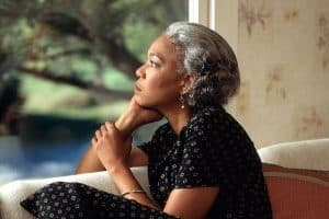 pensive older woman looking out window