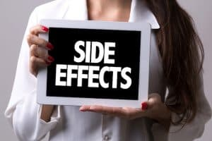 """Woman holding a """"SIDE EFFECTS"""" sign"""