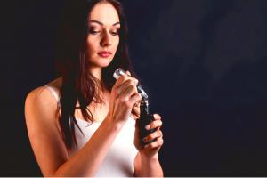 Woman refilling an e-cigarette with vape oil