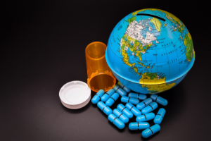 A globe-replica coin bank with an amber pharmacy vial with its blue med capsules spilled out