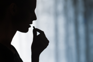 A woman's silhouette showing her taking in a medicine capsule