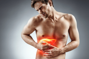 Shirtless man painfully clutching on the right side of his abdomen
